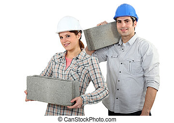 craftsman and craftswoman carrying heavy stone blocks