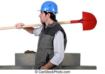 craftsman carrying a shovel on his shoulder