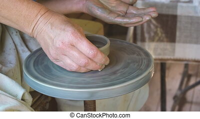 Craftsman creating cup on pottery wheel in slow motion on ...