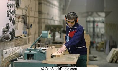 Craftsman cutting wooden plank with circular saw - Skilled...
