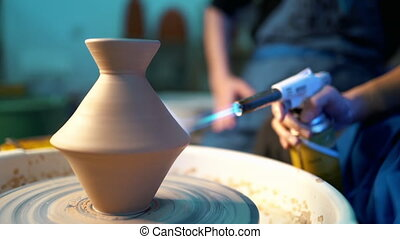 Craftsman finishes the creation of clay jug in his workshop....
