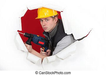 craftsman holding a drill and breaking a paper wall