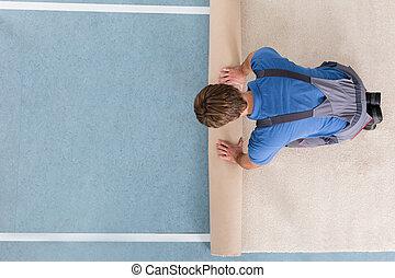 Craftsman In Overalls Unrolling Carpet