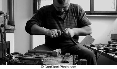 Craftsman is making figure with metal wire in his workshop....