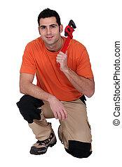 craftsman kneeling holding a spanner