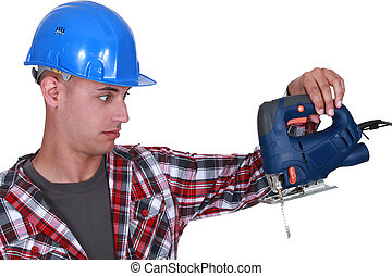 craftsman looking at his drill very surprised