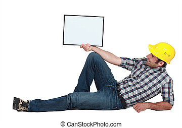 craftsman lying and holding a blank board