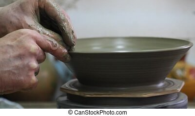 Craftsman making plate from clay - Craftsman making plate on...