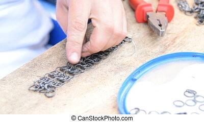 Craftsman making ring armour - Close-up shot of a mam making...
