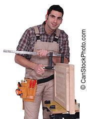 craftsman measuring a window frame