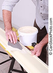 craftsman painting a board