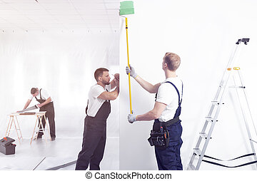 Craftsman painting white wall on green while finishing interior