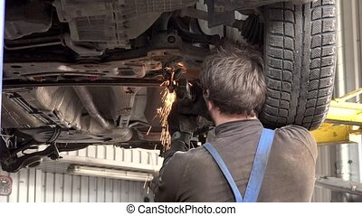 Craftsman repair a car with angle grinder. Glowy sparks...