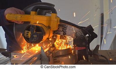 Craftsman sawing metal with disk grinder in workshop. - ...