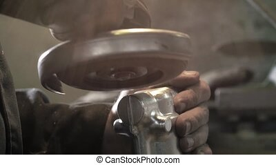 Craftsman sawing metal with disk grinder in workshop, modern iron factory