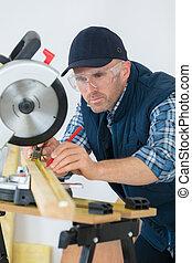 craftsman sawing metal with disk grinder in workshop