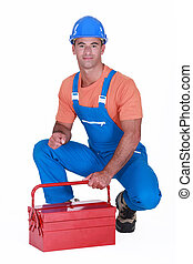 craftsman squatting with toolbox