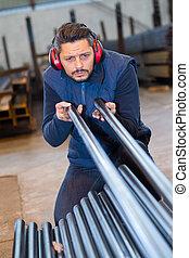 craftsman taking measurements of metal bars