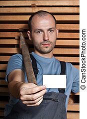 Craftsman with a hammer holding a business card