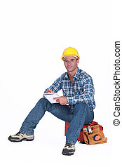 Craftsman with notebook sitting on toolbox