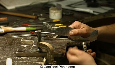 Craftsman working with metal detail. Specialist working with...