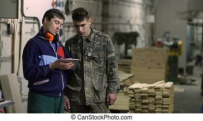 Craftsmen working with tablet pc at carpentry shop -...
