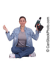 craftswoman holding a drill and meditating