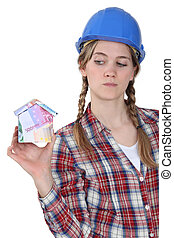 craftswoman holding a little model of house made of banknotes