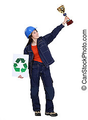 craftswoman holding a recycling label and a golden cup
