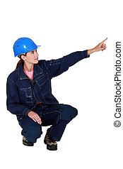 craftswoman pointing at something