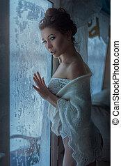 Beautiful girl sly looks standing near the winter window.