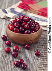 Cranberries in a bowl on wooden table
