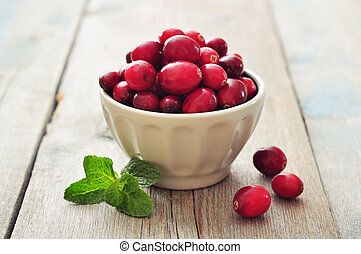 Cranberries in ceramic bowl on wooden background closeup