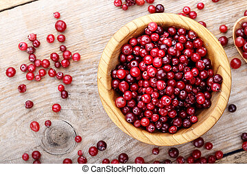 Cranberry in a wooden plate on a wooden background. place for text