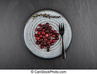 Cranberries with plate on shale