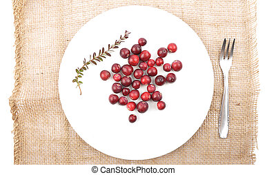Cranberries with twig and plate on jute