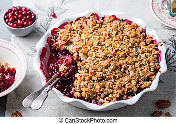 Cranberry crumble, crisp in a baking dish. Grey background. ...