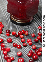 Cranberry jam in glass jars. Cranberries are scattered nearby. On wooden boards with a beautiful texture.