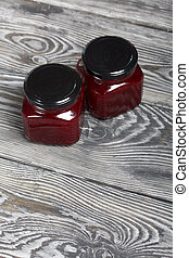 Cranberry jam in glass jars. On wooden boards with a beautiful texture.