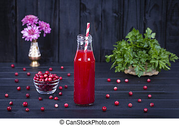 Cranberry juice in a glass bottle and raw cranberry on black wooden background, close up