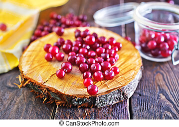 cranberry on the wooden board and on a table