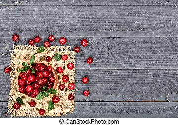 Cranberry with leaf in bowl on black wooden background with copy space for your text. Top view