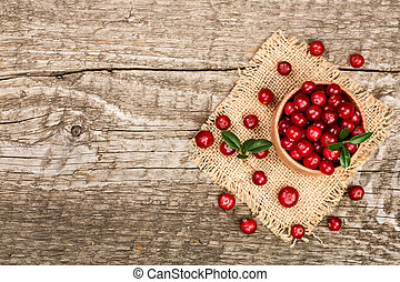 Cranberry with leaf in bowl on old wooden background with copy space for your text. Top view