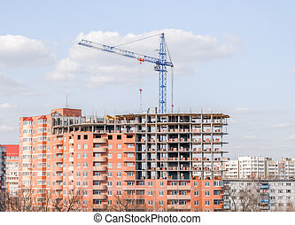 crane against a new block of flats, new multi-storey house.
