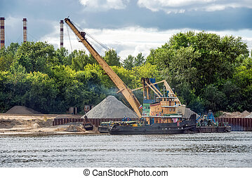 Crane and barge for sand on shore of Volga river at spring cloudy day