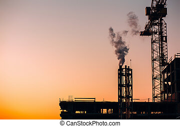 Crane and building construction site with pipe with smoke on background of sunset sky. Industrial landscape with silhouettes of cranes over sunset. Pollution from factory or power plant