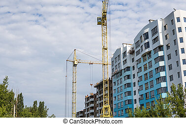 Crane and building under construction against blue cloudy sky.