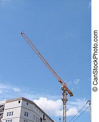 Crane and building under construction against blue sky.