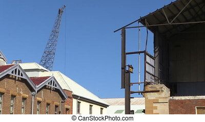 Crane and roof of house - A full shot of a crane and roof of...