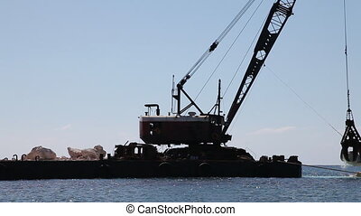 Crane at work on a stone block dam